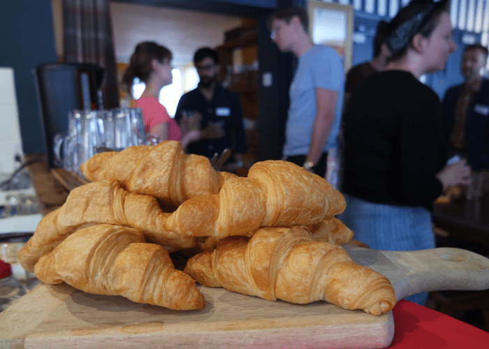 a pile of croissants while people mingle