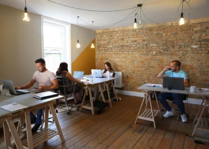 Four people working at hotdesks in The Wheelhouse Cheltenham